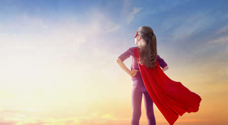 Little child girl playing superhero. Child on the background of sunset sky. Girl power concept Stock fotó