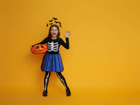 Happy Halloween! Cute little girl in skeleton costume with pumpkin on yellow background. Imagens