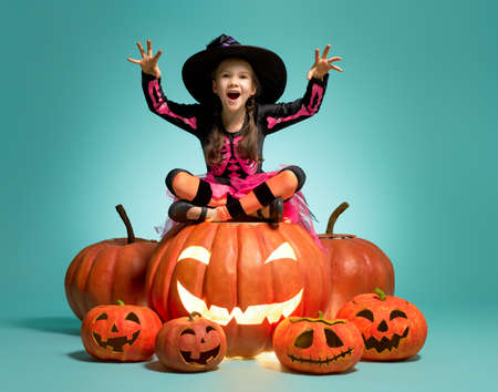 Happy Halloween! Cute little witch with a pumpkin on turquoise background.