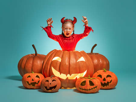 Happy Halloween! Cute little devil with pumpkins on turquoise background. Imagens