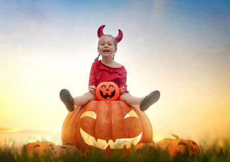 Happy Halloween! Cute little devil with pumpkins. Beautiful young child girl in costume outdoors. Imagens