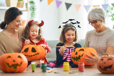 Happy family celebrating Halloween. Grandmother, mother and children at home.