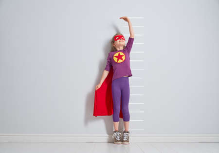 Little child is playing superhero. Kid is measuring the growth on the background of wall. Girl power concept. Stok Fotoğraf