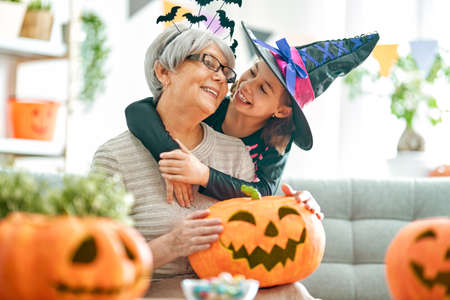 Happy family celebrating Halloween. Grandmother and child at home.