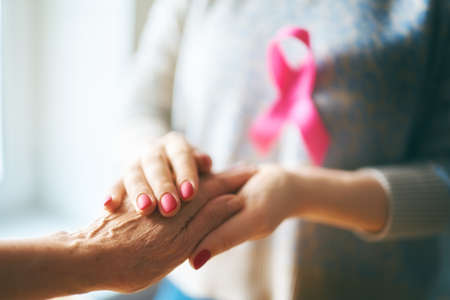 Females hands. Close up. Pink ribbon like a symbol of Breast Cancer Awareness.