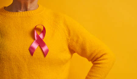 Senior woman on color yellow