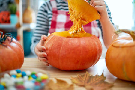 Happy Halloween! Woman is carving pumpkin. Family preparing for holiday.