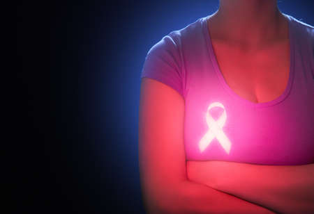 Luminescent pink ribbon like a symbol of breast cancer awareness. Imagens