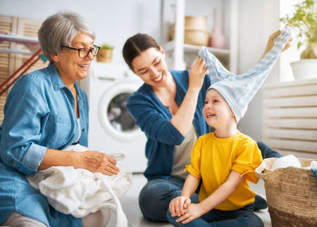 grandma, mom and child are doing laundry at home. three generations of family