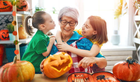 Happy family preparing for Halloween. Grandmother and children at home.