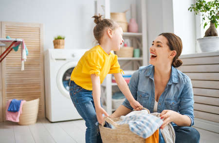 Beautiful young woman and child girl little helper are having fun and smiling while doing laundry at home. Stock fotó
