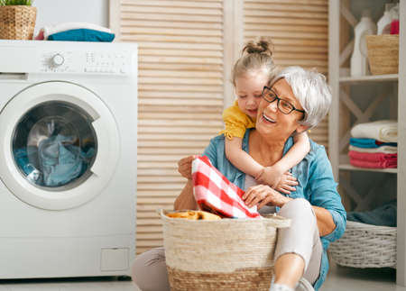 Happy grandma and child girl little helper are having fun and smiling while doing laundry at home.
