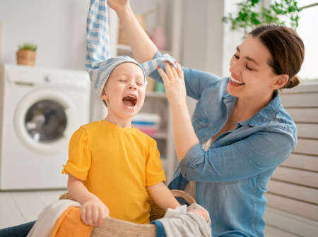 Beautiful young woman and child girl little helper are having fun and smiling while doing laundry at home. Imagens