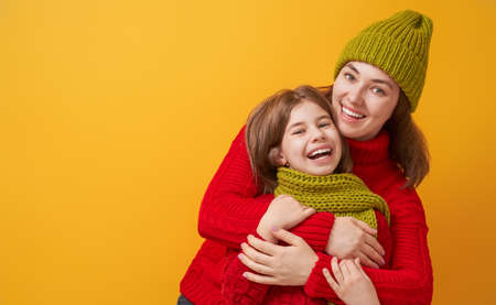 Winter portrait of happy loving family wearing knitted hats, snoods and sweaters. Mother and child girl having fun, playing and laughing on yellow background. Fashion concept.