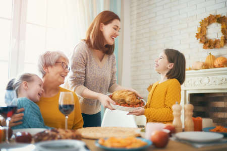 Happy Thanksgiving Day! Autumn feast. Family sitting at the table and celebrating holiday. Traditional dinner. Grandmother, mother and daughters. Stockfoto - 131283097