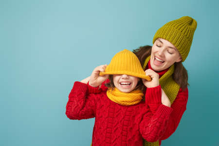 Winter portrait of happy loving family wearing knitted hats, snoods and sweaters. Mother and child girl having fun, playing and laughing on teal background. Fashion concept.