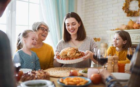Alles Gute zum Erntedankfest! Herbstfest. Familie, die am Tisch sitzt und Feiertag feiert. Großeltern, Mutter, Vater und Kinder. Traditionelles Abendessen. Standard-Bild