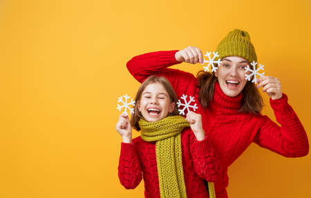 Winter portrait of happy loving family wearing knitted hats, snoods and sweaters. Mother and child girl having fun, playing and laughing on yellow background. Fashion concept. 版權商用圖片 - 132114217