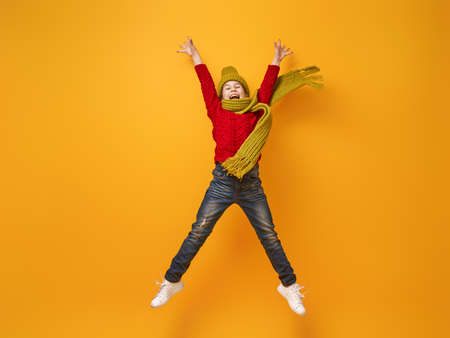Winter portrait of happy child wearing knitted hat, snood and sweater. Girl having fun, playing and laughing on yellow background. Fashion concept.