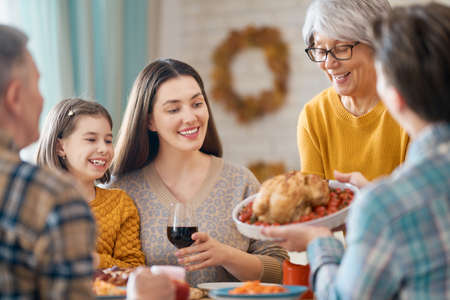 Happy Thanksgiving Day! Autumn feast. Family sitting at the table and celebrating holiday. Grandparents, mother, father and children. Traditional dinner.                                Banque d'images