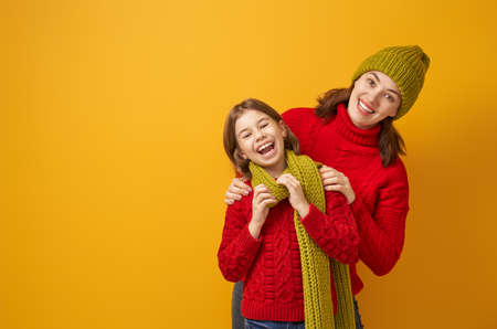 Winter portrait of happy loving family wearing knitted hats, snoods and sweaters. Mother and child girl having fun, playing and laughing on yellow background. Fashion concept. 版權商用圖片 - 132113759