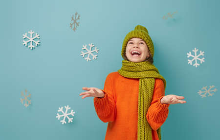 Winter portrait of happy child wearing knitted hat, snood and sweater. Girl having fun, playing and laughing on teal background. Fashion concept. 版權商用圖片 - 132113795
