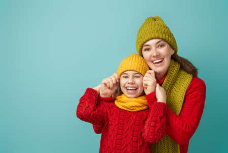 Winter portrait of happy loving family wearing knitted hats, snoods and sweaters. Mother and child girl having fun, playing and laughing on teal background. Fashion concept. Stock Photo - 132121318