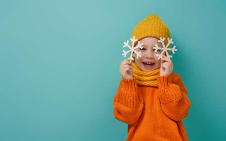 Winter portrait of happy child wearing knitted hat, snood and sweater. Girl having fun, playing and laughing on teal background. Fashion concept. 版權商用圖片 - 132121769
