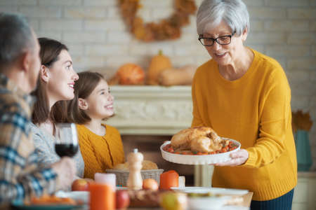 Happy Thanksgiving Day! Autumn feast. Family sitting at the table and celebrating holiday. Grandparents, mother and child. Traditional dinner.