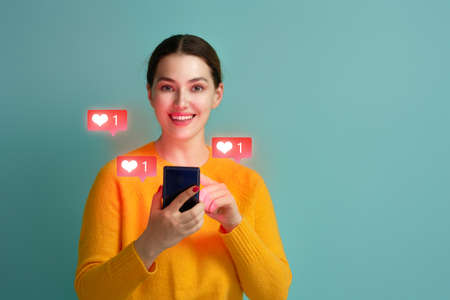 Young woman is using smartphone. Happy girl on teal background. Social media concept. Heart icons.