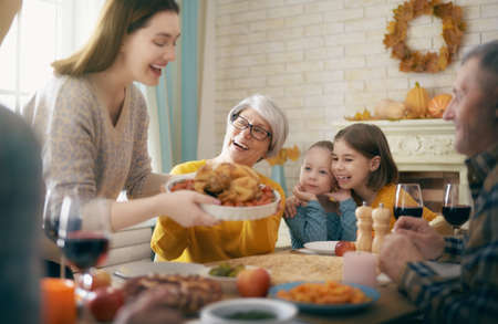 Happy Thanksgiving Day! Autumn feast. Family sitting at the table and celebrating holiday. Grandparents, mother, father and children. Traditional dinner.                                Banco de Imagens