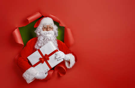 Merry Christmas and Happy Holidays! Santa Claus with present on bright color background.