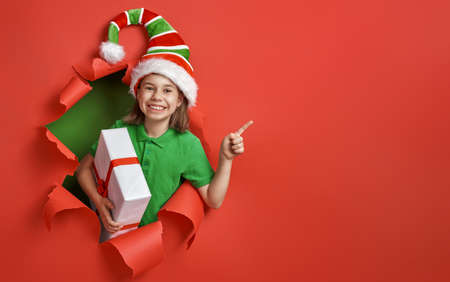 Merry Christmas! Little girl in Santa's elf costume on bright color background. Red and green. Stockfoto