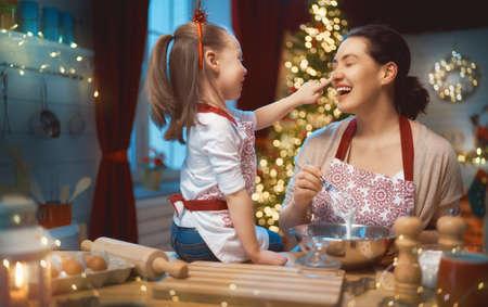 Feliz Navidad y felices fiestas. Preparación familiar comida de vacaciones. Madre e hija cocinando galletas.