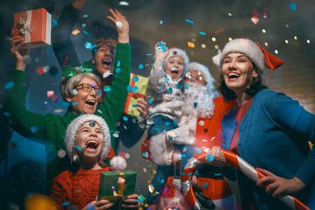 Prettige kerstdagen en fijne feestdagen! Oma, opa, mama, papa en kinderen hebben plezier in de buurt van de boom binnenshuis. Familiefeest. Stockfoto