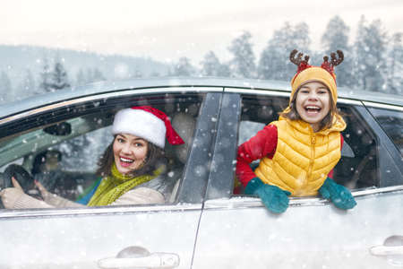 Toward adventure! Happy family are relaxing and enjoying road trip. Mother, child and car on snowy winter nature background. Christmas holidays time.