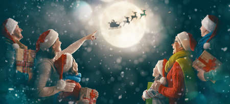 Merry Christmas and happy holidays! Family enjoying the christmas watching santa in the sky on dark background. Stock Photo