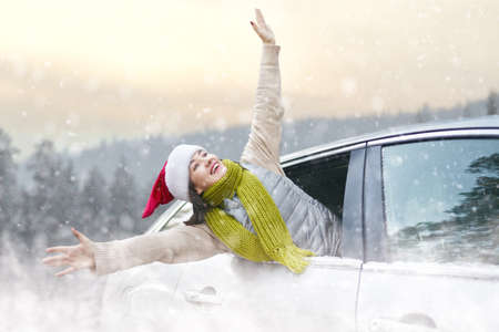 Toward adventure! Happy woman is relaxing and enjoying road trip. Girl and car on snowy winter nature background. Christmas holidays time.                                                               Stock Photo
