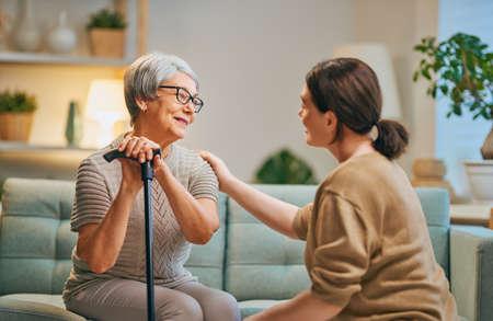 Zadowolony pacjent i opiekun spędzający razem czas. Starsza kobieta trzyma trzcinę. Zdjęcie Seryjne