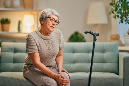 Ältere Frau mit Stock. Unwohlsein und Schmerzen im Knie. Standard-Bild