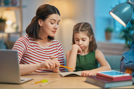 Zurück zur Schule. Glückliches Kind sitzt am Schreibtisch. Mädchen, das Hausaufgaben macht.