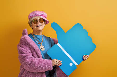 Portrait of funny senior woman on color background.  Stock Photo