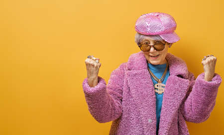 Portrait of funny senior woman on color background.