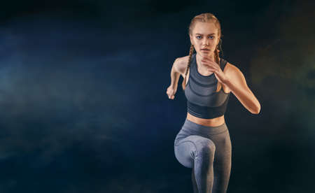 Healthy lifestyle and sport concepts. Woman in fashionable sportswear is doing exercise. Girl is running jogging.