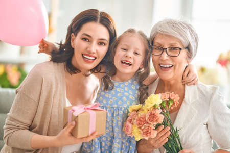 Happy women's day! Child daughter is congratulating mom and granny. Grandma, mum and girl smiling and hugging. Family holiday and togetherness.