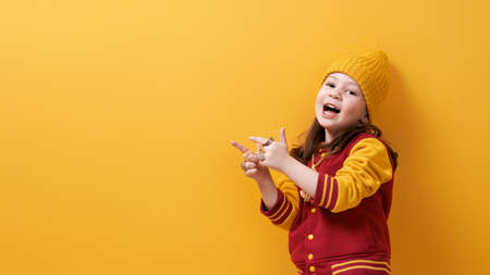 Portrait of a cute little girl in fashionable clothes. Hip-hop style. Kid on bright color background. Фото со стока