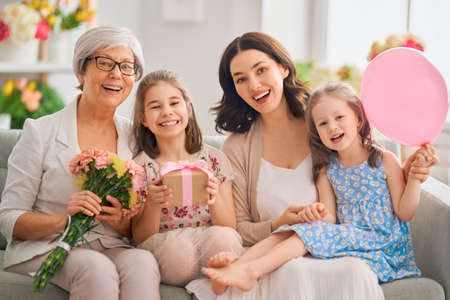 Happy women's day! Children daughters are congratulating mom and granny giving them flowers and gift. Grandma, mum and girls smiling and hugging. Family holiday and togetherness.