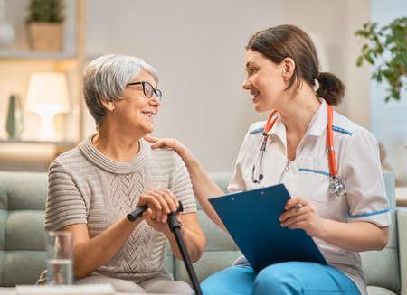 Glücklicher Patient und Betreuer, die Zeit miteinander verbringen. Ältere Frau, die Stock hält. Standard-Bild