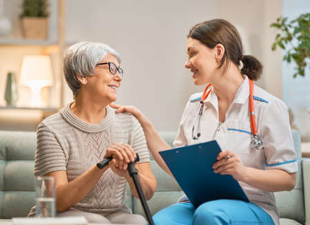 Paziente e caregiver felici che trascorrono del tempo insieme. Senior donna azienda canna. Archivio Fotografico