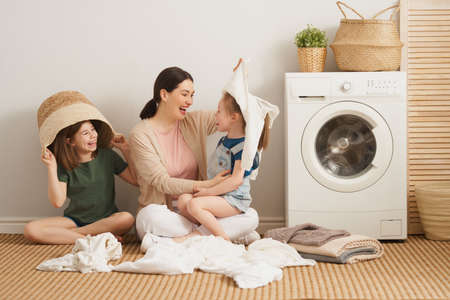 Beautiful young woman and children girls little helpers are having fun and smiling while doing laundry at home.